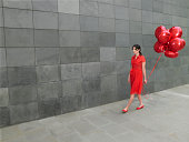 Young woman walking along holding bunch of red foil balloons