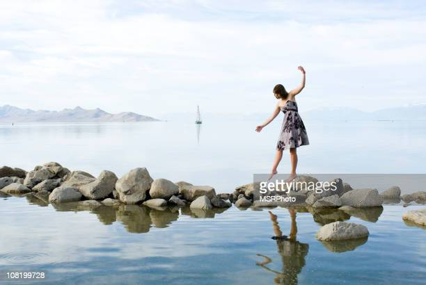 Young Woman Walking Along lake Rocks
