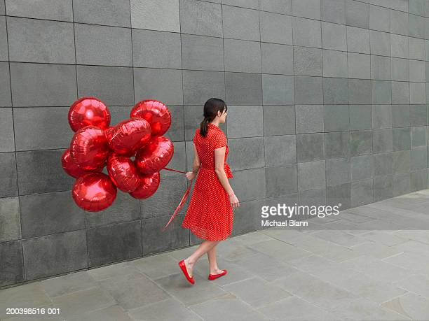 Young woman walking along with bunch of red foil balloons, rear view