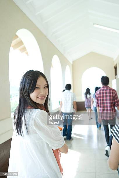 Young woman walking and looking back in corridor