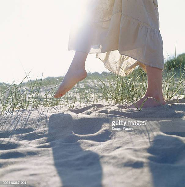 Young woman walking bare foot on sandy beach, low section