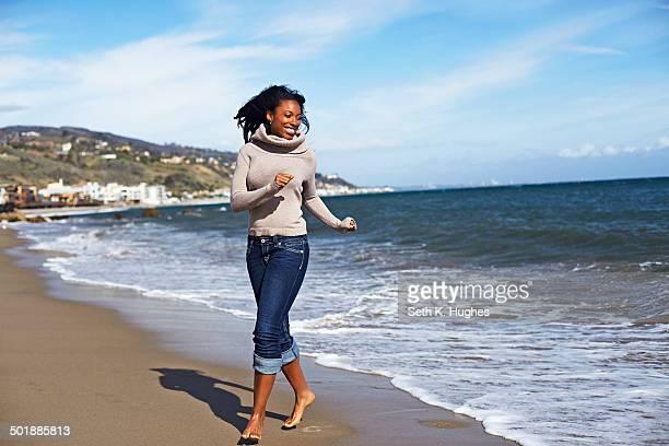 Young woman walking barefoot on beach, Malibu, California, USA