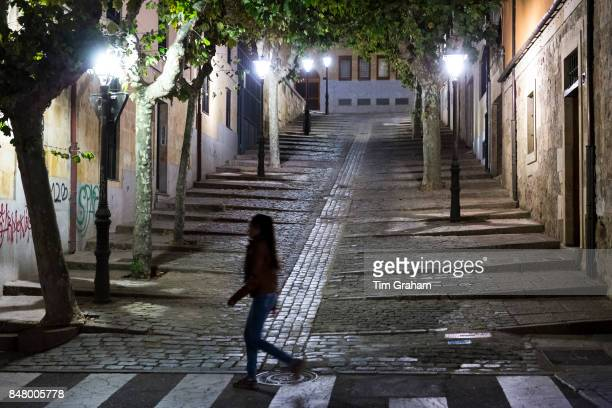young woman walking by Cuesta de Carvajal cobbled street in Salamanca Spain