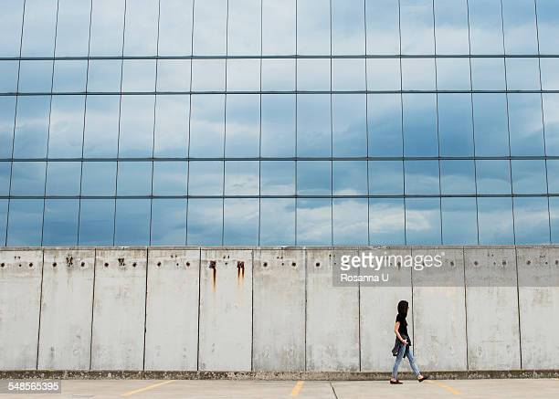 Young woman walking by modern building