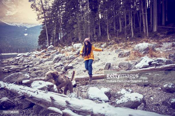 Young woman walking dog by snowy Lake Eibsee, Zugspitze, Bavaria, Germany