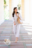 Young woman walking dog in portico