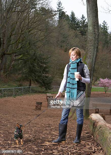 Young woman walking dog on leash in dog park, spring