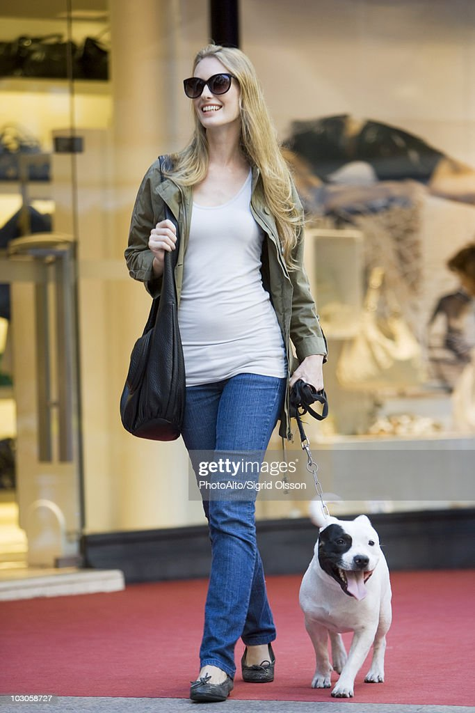 Young woman walking dog : Stock Photo