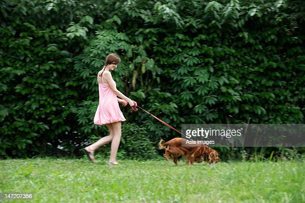 Young woman walking dog