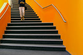 Young person walking down orange stairs