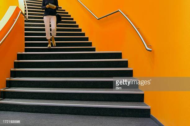 Young woman walking down orange stairs, reading book