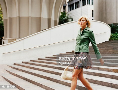 Young Woman Walking Down Steps by a Building in the City : Stockfoto