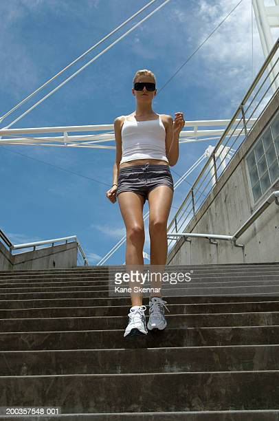 Young woman walking down steps, low angle