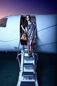 Young woman walking down steps of private jet