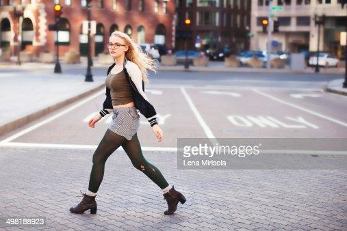 Young woman walking down street