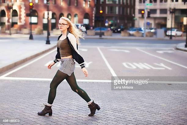 Young woman walking down street