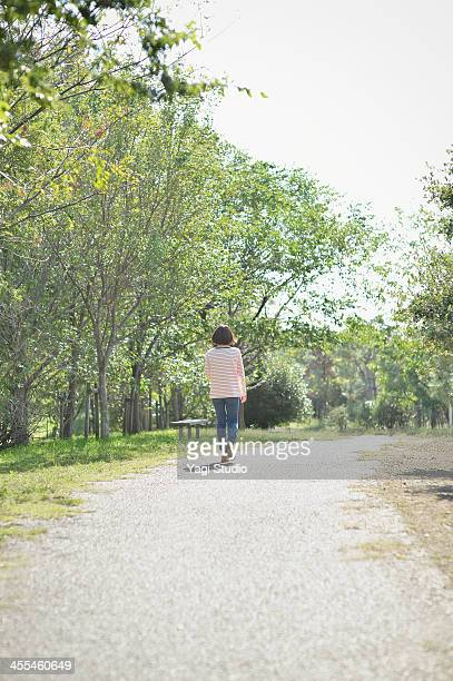 Young woman walking down the street in the park