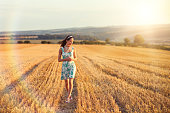 Young Woman Walking in Countryside Field