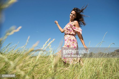 Young woman walking in field with arms raised : Photo