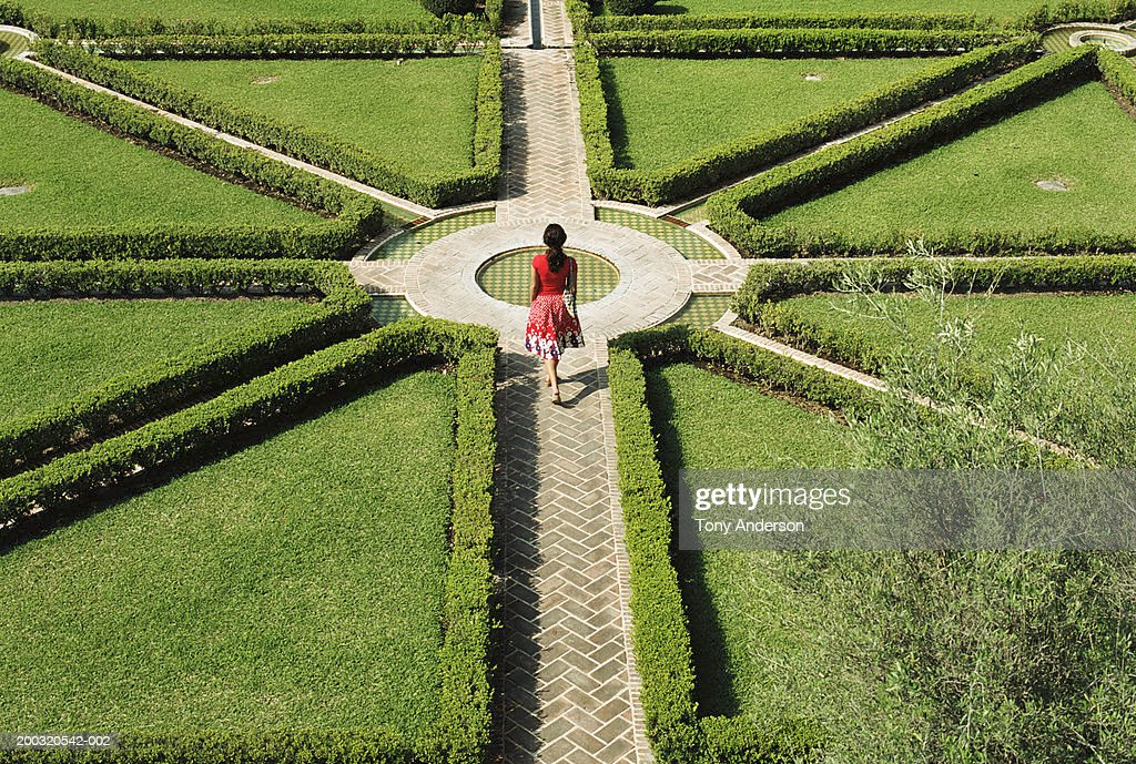 Young woman walking in formal garden, elevated view