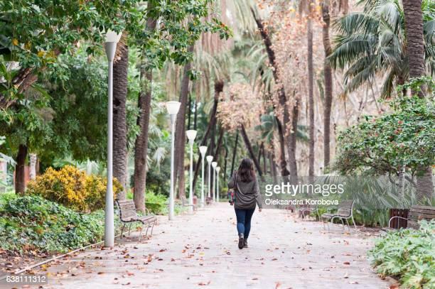 Young woman walking in lush green tropical gardens in Malaga, Andalusia, Spain