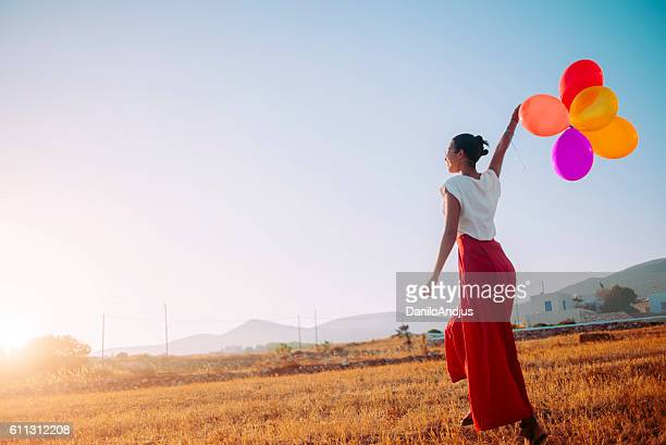 young woman walking in the field holding colorful balloons