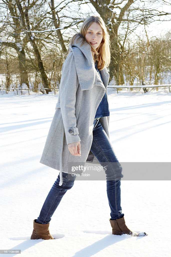 Young woman walking in the snow : Stock Photo