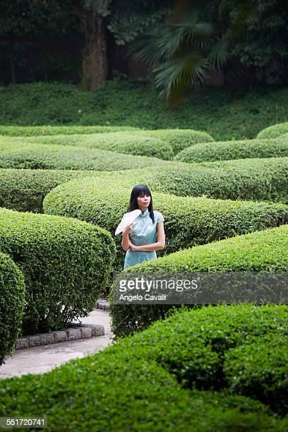 Young Woman Walking in Topiary Garden