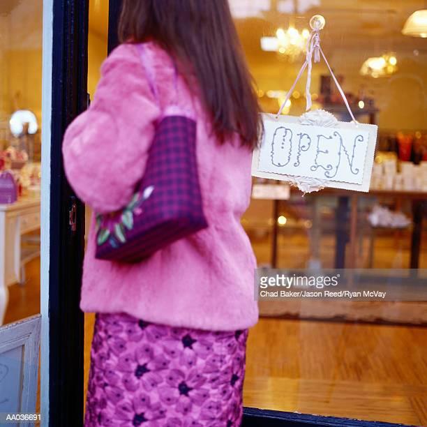 Young woman walking into shop, rear view