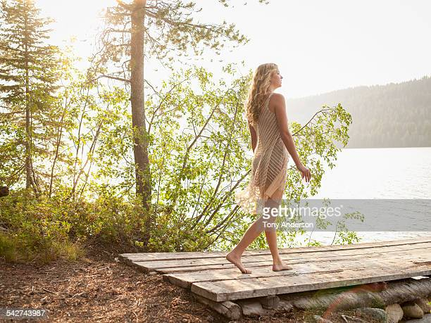 Young woman walking near mountain lake