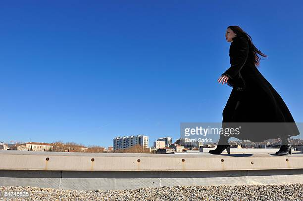 Young woman walking on a building roof