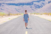 Young woman walking on an endless straight empty road in the middle of nowhere on the Route 66 road. Backpackers, visionary, entrepreneur, adventure concepts.