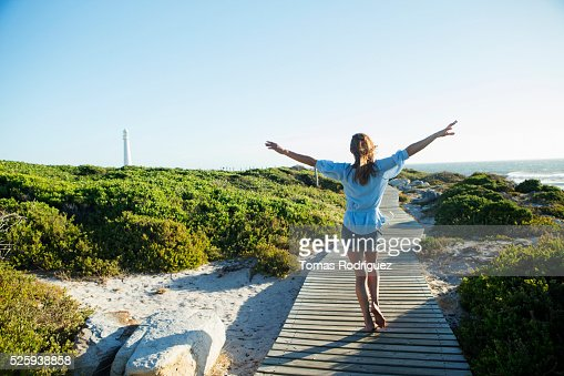Young woman walking on boardwalk : Stock Photo