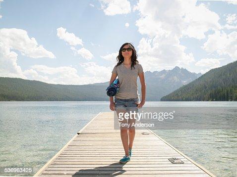 Young woman walking on dock at mountain lake