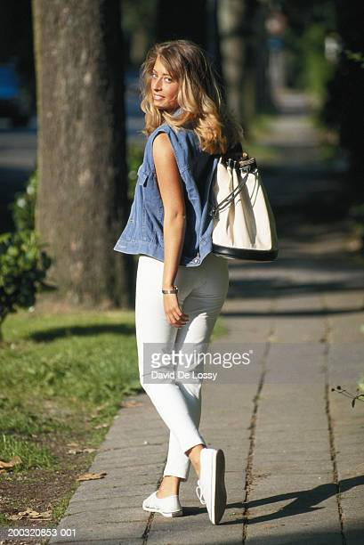 Young woman walking on footpath, looking over shoulder