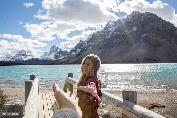 Jeune femme marchant sur le pont en bois de la main de l'homme