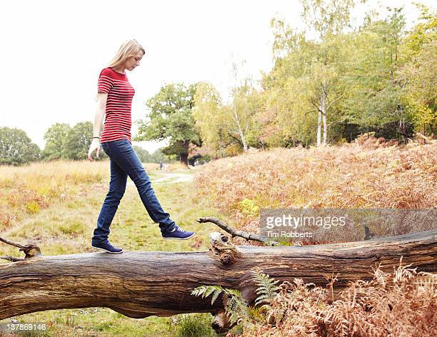 Young woman walking on log.