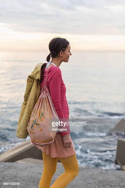 Junge Frau zu Fuß auf dem pier in Herbst Sonnenaufgang