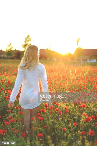 Young woman walking on poppy field