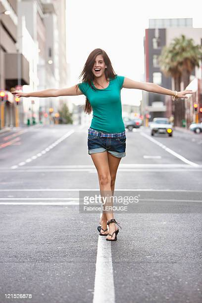 Young woman walking on road marking and balancing herself