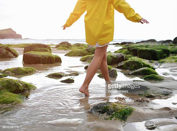 Young woman walking on rocky beach