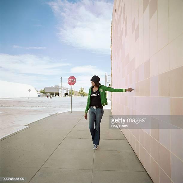 Young woman walking on sidewalk, touching wall