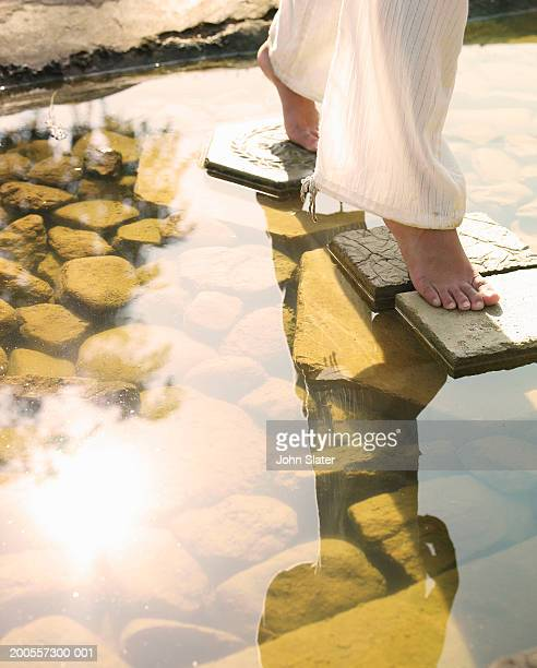 Young woman walking on stepping stones