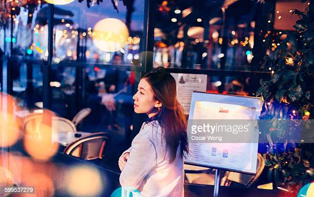 Young woman walking on street at night, Paris