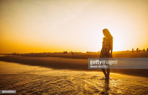 Young woman walking on the beach Praia do Barril in a sunset, deTavira city, region of Algarve, Portugal