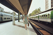 Young woman walking on train platform, rear view