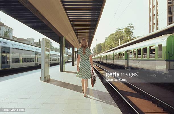 Young woman walking on train platform, rear view
