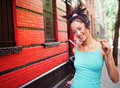 Young woman walking on urban street wearing headphones