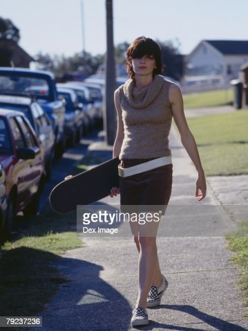 Young woman walking on walkway, holding a skateboard : Stock Photo
