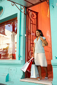 Young woman walking out of shop, carrying bags, low angle view